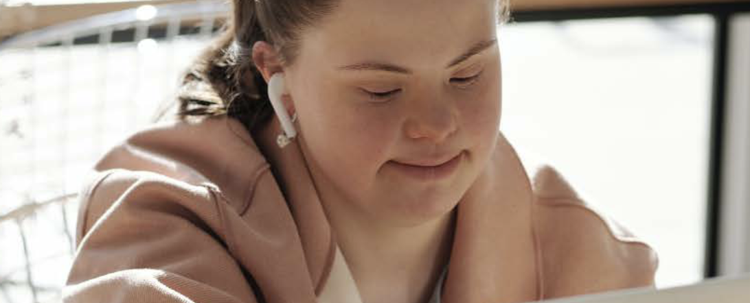 Woman with Down Syndrome wearing headphones and smiling at her computer. She is wearing a pink jacket and has her brown hair tied in a pony tail.