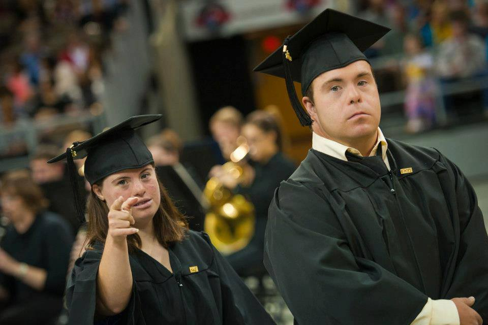 Two students with down syndrome wearing a cap and gown at their college graduation